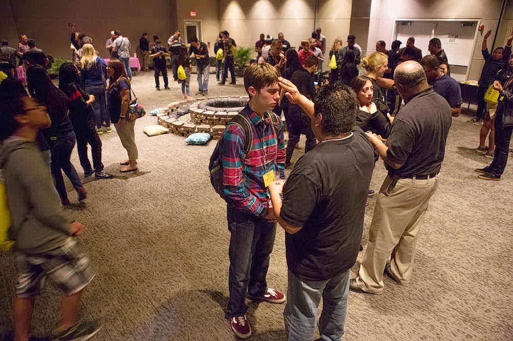 Пастор Мэнни Крус, молодежный директор Аризонской Конференции, молится с участником конференции. (Дэн Вебер / NAD)