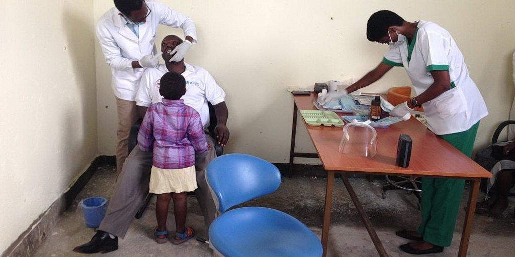 Девочка наблюдает как стоматолог-гигиенист проверяет зубы ее отца в воскресенье в бесплатной клинике в Гюзний, Руанда. (Эндрю МкЧесни AR)