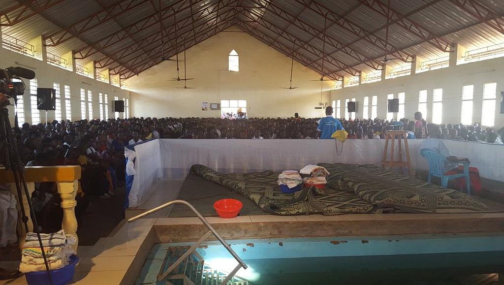 Переполненная церковь Кабусунзу в субботу. Коврики приготовлены на платформе перед крещениями. (Нэнси Коста)