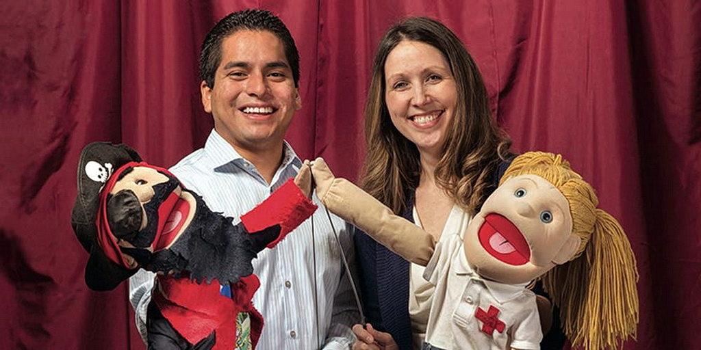 Марко Паско-Рубио, ученик Школы общественного здравоохранения и Ронда Спенсер-Хванг, доктор общественного здравоохранения, демонстрируют куклы, которые они используют в работе просвещения населения в области здравоохранения. [Фото: LLSPH]