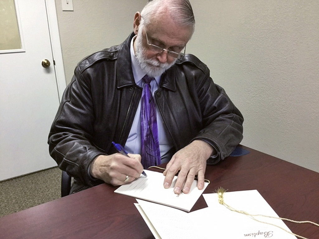 Пастор Тед Уильямс подписывает свидетельства о крещении трех мужчин в Исправительном учреждении округа Кроули в Олни Спрингс, Колорадо, Соединенные Штаты. [Фото: Раймунд Дабровский]