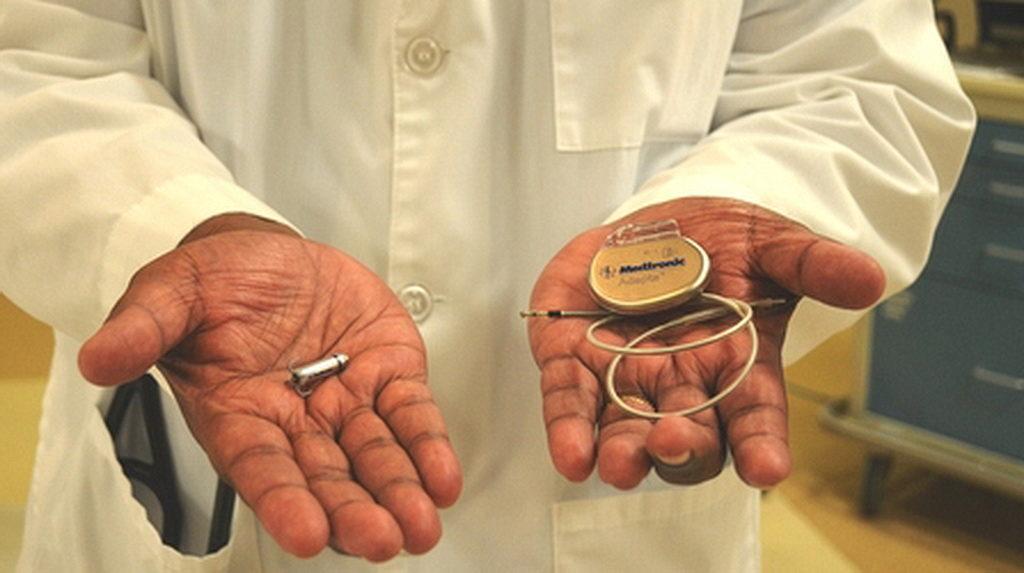 Врач держит систему Micra® Transcatheter Pacing System, слева, и сравнивает ее с традиционными кардиостимуляторами, справа, для которых требуются сердечные провода (также известные как выводы) и громоздкий хирургический «карман» под кожей. Флоридский больничный мемориальный медицинский центр и больница Флориды Новая Смирна недавно начала предлагать самый маленький кардиостимулятор в мире. [Фото: Новости Флоридской больницы]