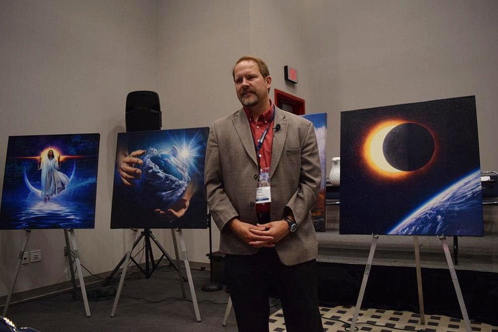 Позади Райана Хейса, некоторые картины Натана Грина, которые будут использоваться в новых наборах материалов, чтобы понять химию на основе каждого дня истории творения. [Фотография: Маркос Паседжи, Adventist Review]