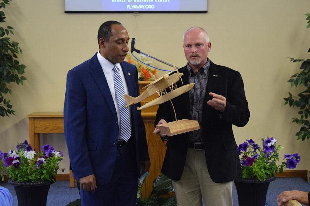Президент конференции Онтарио Мэнсфилд Эдвардс получает деревянную копию нового самолета миссии для канадского Севера от Джада Виквайра, вице-президента AWA по операциям. [Фото: Маркос Паседжи, Adventist Review]