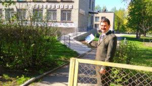 Геннадий Кузнецов встречает людей у входа в библиотеку