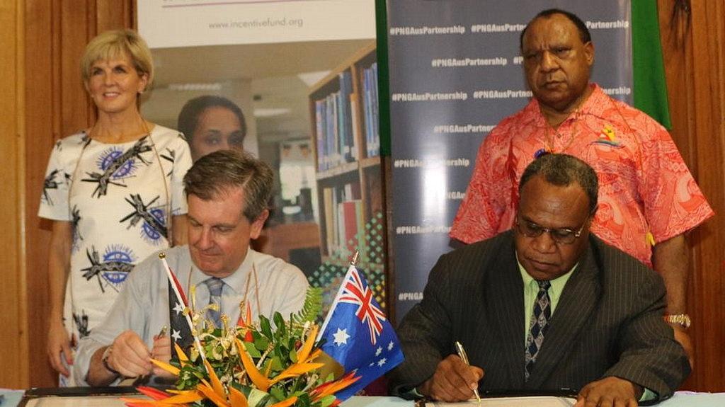 Верховный комиссар Австралии в PNG Брюс Дэвис и председатель правления ADRA PNG и президент унионной миссии Папуа-Новой Гвинеи Кепси Элодо подписывают проектное соглашение. [Фото: ADRA PNG]