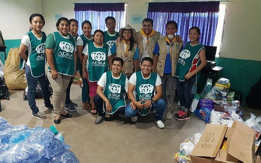 Группа добровольцев позирует для фотографии, прежде чем сортировать еду и воду для перемещенных семей в сельских общинах вблизи вулкана Огня в южной центральной Гватемале. [Фото: ADRA Гватемала, Новости Интер-Американского дивизиона ]