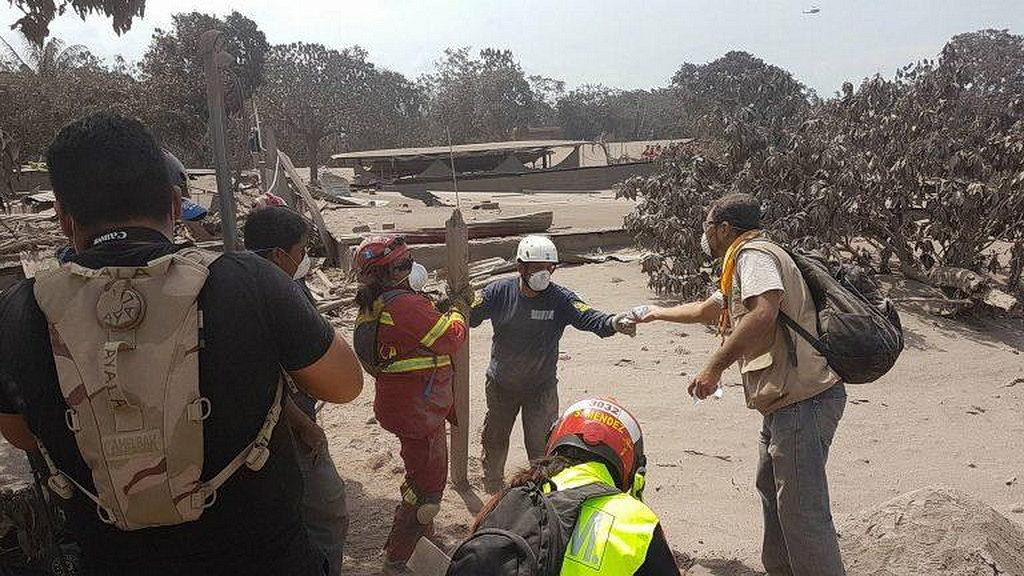 Волонтеры ADRA доставляют воду команде реагирования на чрезвычайные ситуации в обществе, покрытом лавой и пеплом в Эскуинтле в южном центральном районе Гватемалы, через несколько часов после того, как вулкан Огня начал извержение и накрыл дома и убил десятки людей 3 июня 2018 года. [Фото : ADRA Гватемала, Новости Интер-Американского дивизиона]