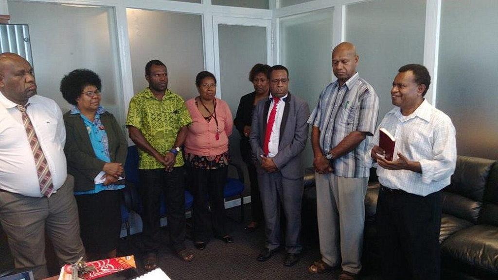Мартин Сангу (справа) говорит на специальном служении посвящения в новом офисе Кони Сэмюэля. [Фотография: Adventist Record]