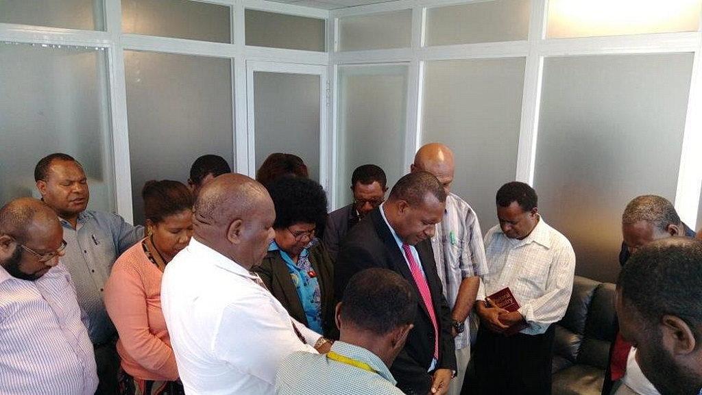 Рекс Кой (второй слева) возносит молитву посвящения за Кони Сэмюэля (в центре) и его сотрудников. [Фотография: Adventist Record]