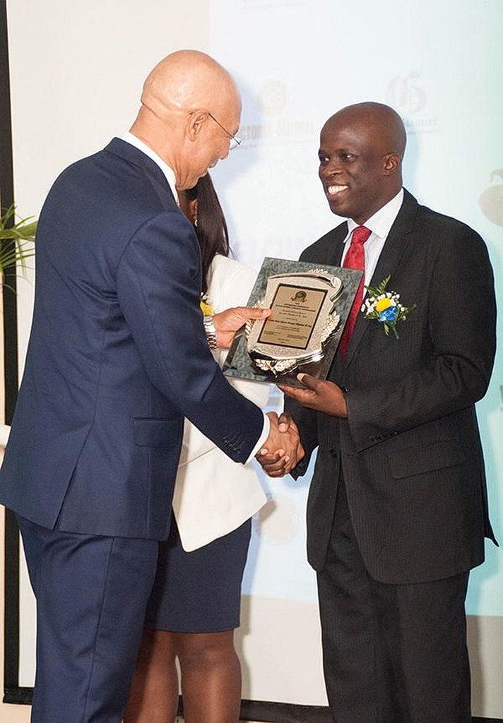 Омар Олифант (справа) принимает свою награду от генерал-губернатора Ямайки сэра Патрика Аллена во время вручения наград генерал-губернатора. [ Фото: Чавар Льюис, Новости Интер-Американского дивизиона]