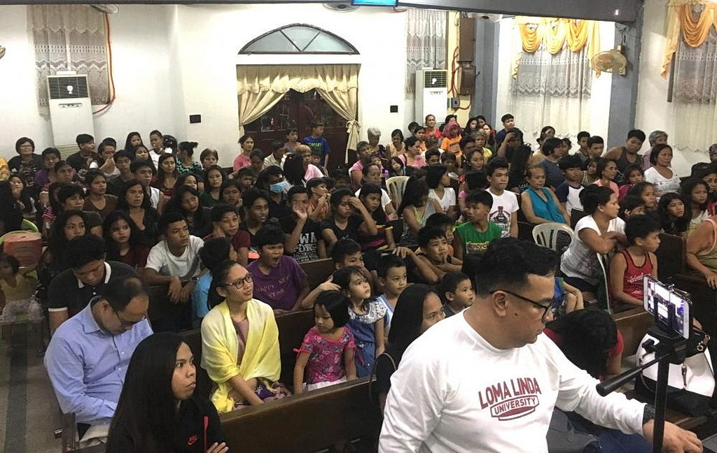 Участники встречи теснятся на одном из более чем 40 мест в Маниле, где в июле 2018 года состоялись евангелизационные встречи. [Фото: Новости служения «Так Написано»]