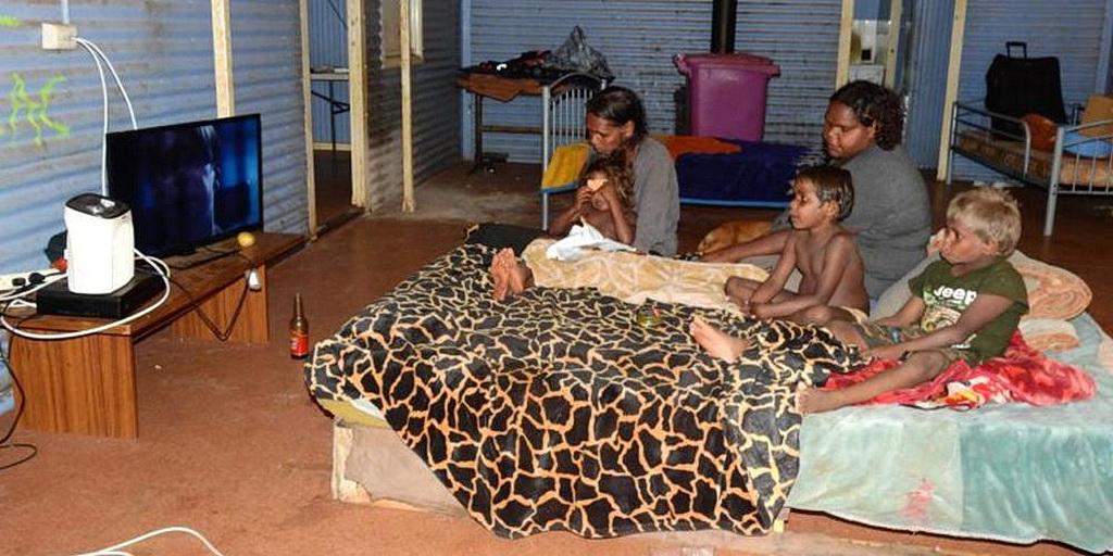 Семья коренных народов, живущая в отдаленном сообществе Австралии, смотрит телевизор. Вера FM, радиостанция адвентистов седьмого дня, теперь доступна для просмотра в Австралии на 688 канале спутникового телевидения (VAST). [Фото: Дон Фелхберг, Adventist Record]