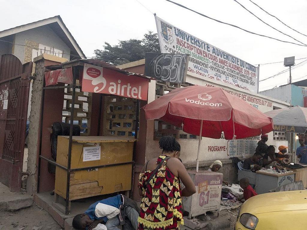 Патрик Кайенд Омугамай начал свой телефонный бизнес со стола и зонтика, а затем перешел в эту деревянную будку. [Фото: Эндрю МакЧесни, Адвентистская Миссия]