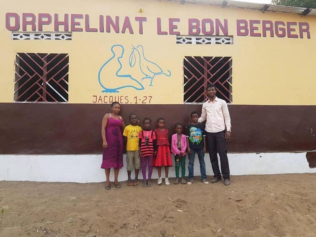 На фото Патрик Кайенд Омугамай и его жена с некоторыми детьми, которых они воспитывают в бывшем приюте Патрика в Киншасе, Демократическая Республика Конго. [Фото: Эндрю МакЧесни, Адвентистская Миссия]