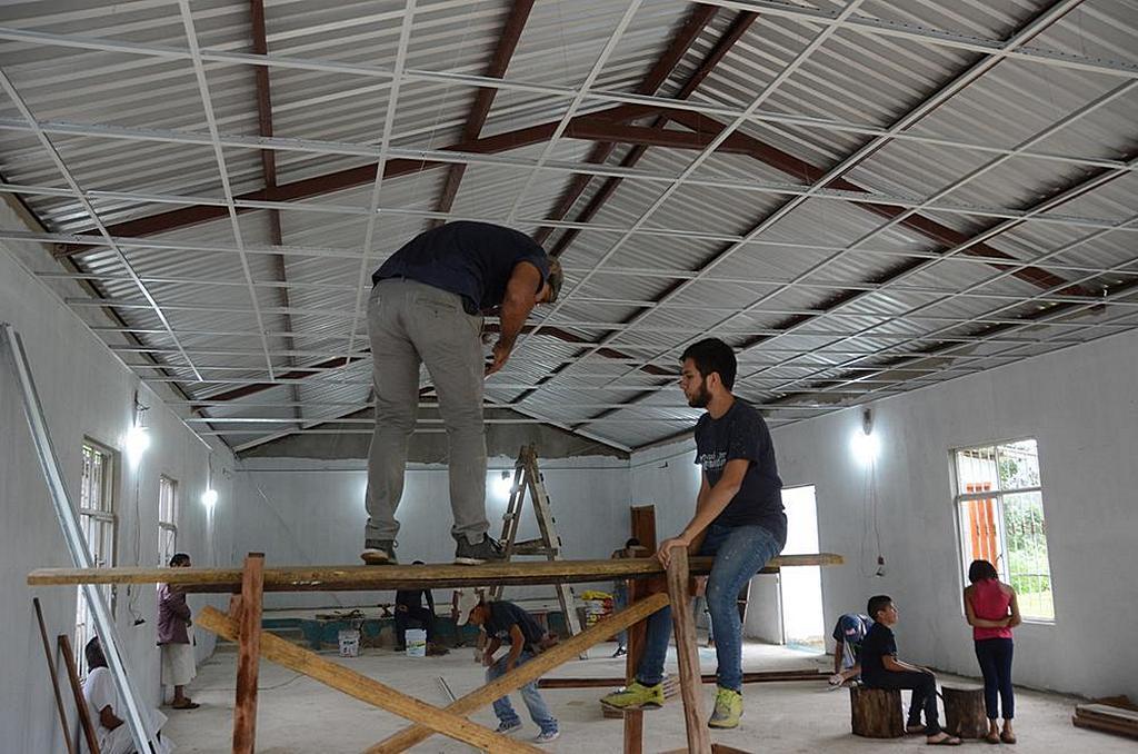 Студенты и волонтеры работают над монажом потолка нового здания церкви за несколько дней до посвящения в декабре 2018 года. [Фото: Университет Монтеморелос]