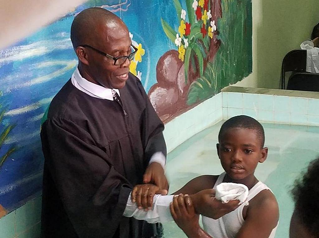 Семилетний Джах-Винчи Карти держит руку Оуэна Томаса, пастора, который крестил его в церкви адвентистов седьмого дня города Тренч в Кингстоне, Ямайка, 9 февраля 2019 года. [Фото: конференция Восточной Ямайки]
