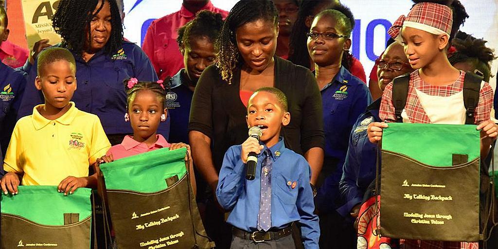Шестилетний Дакарай Уильямс (держит в руках микрофон) делится своими свидетельствами с тысячами людей во время съезда «Господь, измени меня» Интерамериканского дивизиона, проведенного в Конгресс-центре Монтего-Бей на Ямайке 9 февраля 2019 года. [Фото: Конференция Восточной Ямайки]