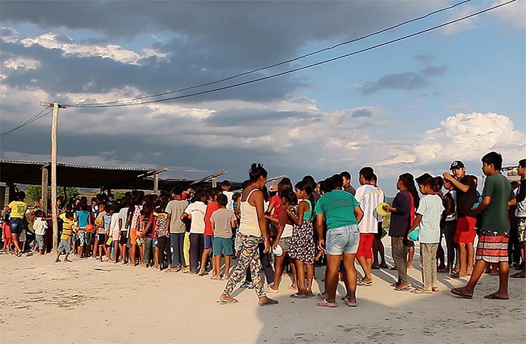 Группа венесуэльских беженцев выстраивается в очередь для получения помощи. Адвентистское Агентство по Развитию и Помощи (ADRA) на северо-западе Бразилии сотрудничает с бразильской армией и другими организациями, чтобы обеспечить продовольствием и одеялами вновь прибывших. [Фото: новости Южно-Американского дивизиона]