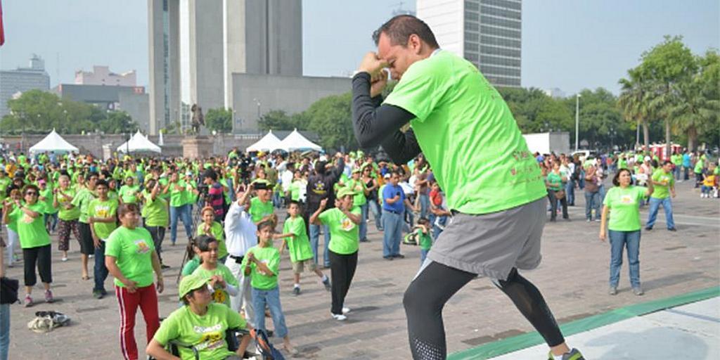 13 апреля 2014 года тренер руководит толпой людей на площади Explanada de los Heroes в Монтеррее, Нуэво-Леон, Мексика, после того как адвентистская церковь раздала около 20 000 салатов во время инициативы по оказанию воздействия на здоровье для пропаганды здорового образа жизни в условиях растущей эпидемии ожирения в стране. Это событие было частью серии мероприятий, проведенных в течение восьми недель в рамках церковной инициативы «Я хочу жить здоровым». [Фото: Альжафет Чабле / IAD]
