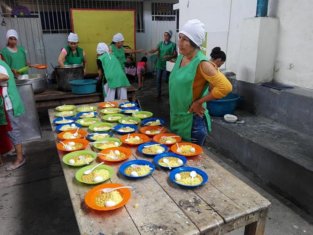 Волонтеры из церкви адвентистов седьмого дня в Эль-Эдене, Кукута, Колумбия, готовятся к раздаче блюд во время обеда в среду. Питание на фото включает рис, нут и яйцо, сваренное вкрутую. [Фото: Хулиан Агудело]