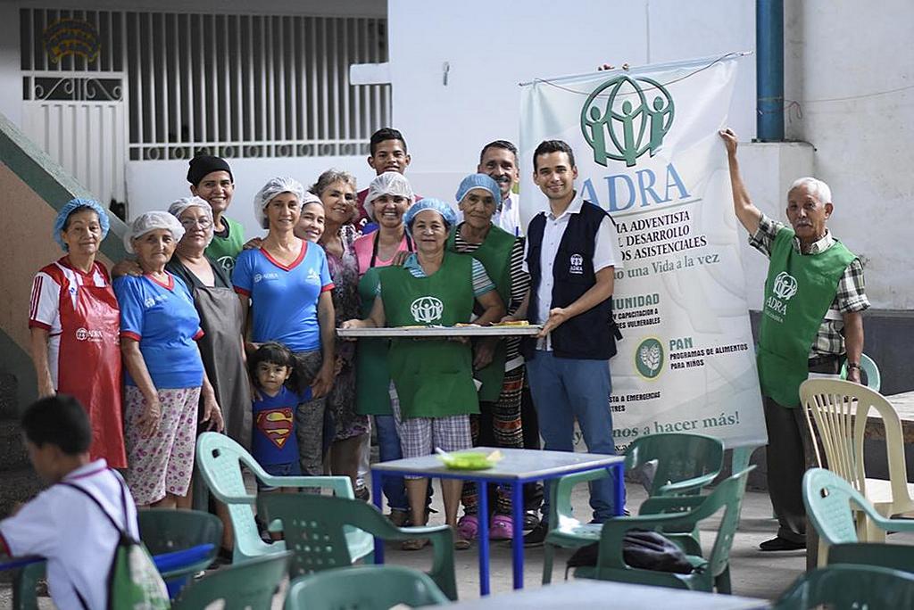 Хулиан Агудело (второй справа), пастор церкви адвентистов седьмого дня Эль-Эдена в Эдене, Кукута, Колумбия, фотографируется с членами церкви, которые каждую неделю добровольно готовят и дают горячую еду более чем 200 людям. [Фото: ADRA Колумбия]