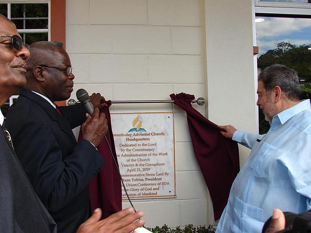 Керн Тобиас (второй слева), президент адвентистской церкви в регионе Карибского униона, говорит, в то время как он и премьер-министр Гонсалвес (справа) открывают мемориальную доску у входа в новое здание штаб-квартиры миссии Сент-Винсент и Гренадины. За этим наблюдает Дермот Батист (крайний слева), президент миссии Сент-Винсент и Гренадин. [Фото: миссия Сент-Винсент и Гренадины]