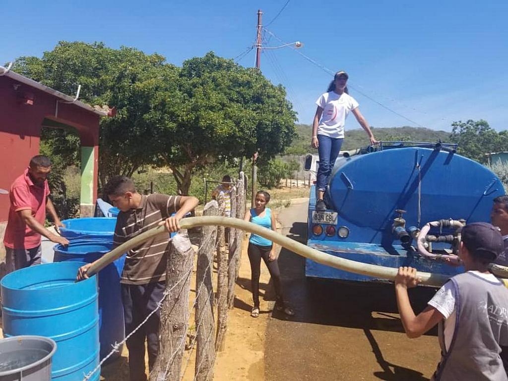 Волонтеры-члены Церкви доставляют питьевую воду в общину Сиенагуита в городе Пуэрто-Кумаребо на западе Венесуэлы. [Фото: Западный Венесуэльский Унион]