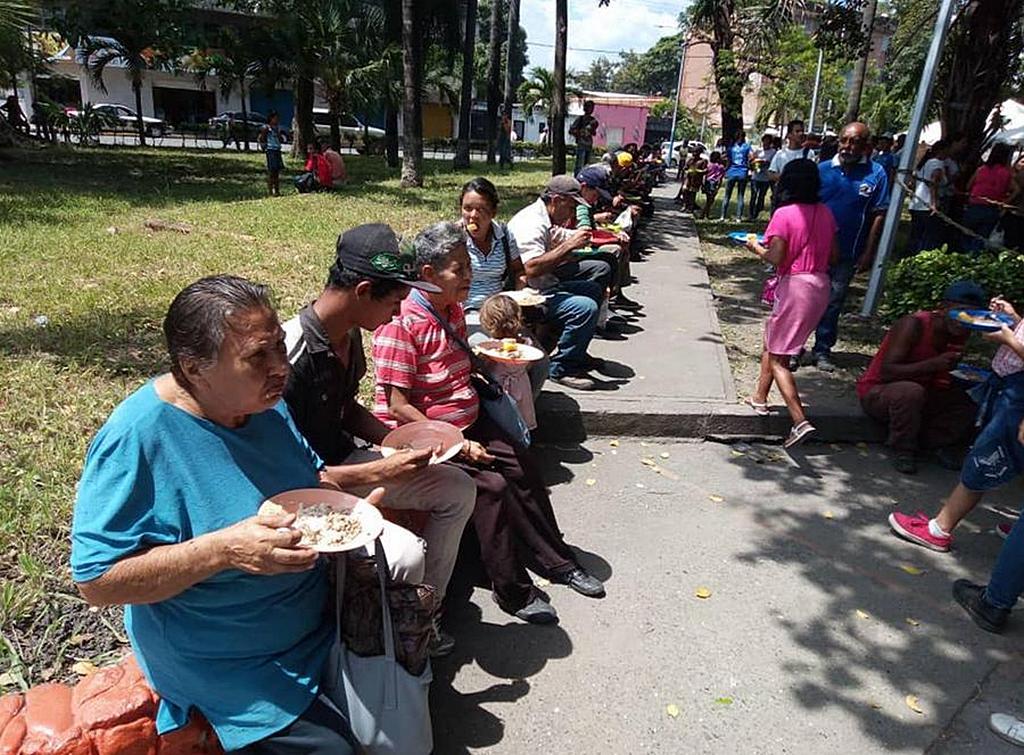 Десятки людей получают тарелку с горячей едой на площади Андрес Элой Бланко в Акаригуа, Венесуэла, во время миссионерской программы адвентистской церкви «Ближе к тебе, Венесуэла» в августе 2019 года. [Фото: Западный Венесуэльский Унион]