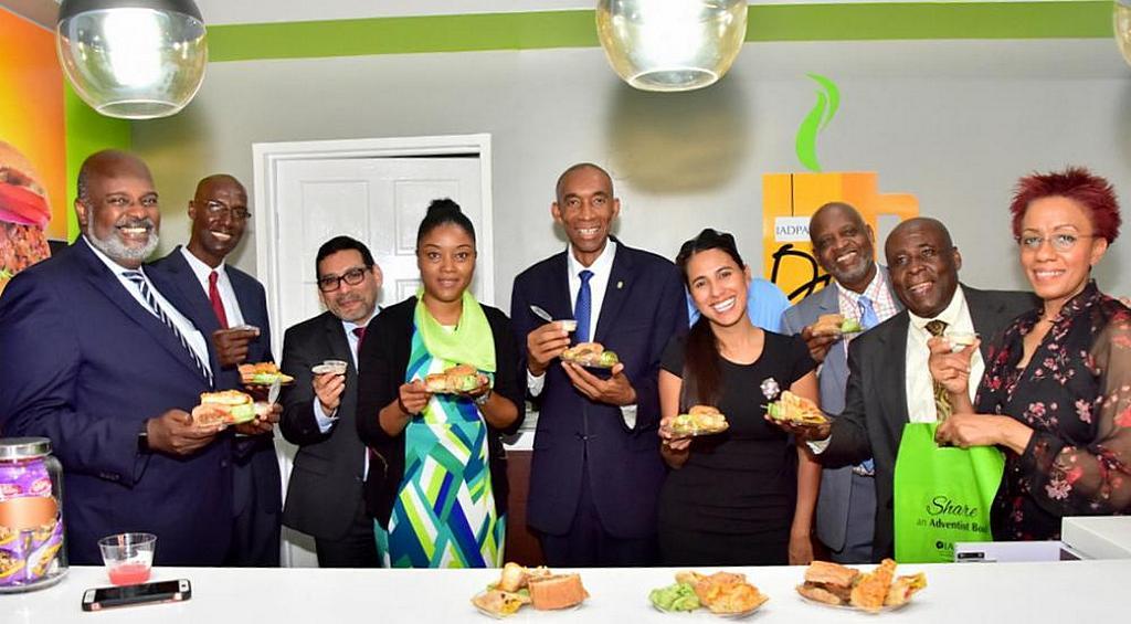 Церковные лидеры Интерамериканского дивизиона (IAD), издательской ассоциации Интерамериканского дивизиона (IADPA) и региона Ямайской Унионной Конференции держат образцы здоровых закусок, которые можно будет купить в новом книжном магазине IADPA в Кингстоне. [Фото: Конференция Восточной Ямайки]