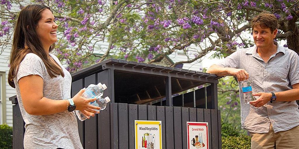 Зои-Элиз Уотсон (слева) и ее преподаватель по экологическим вопросам Джейсон Мортон стоят рядом с новыми двойными 240-литровыми мусорными контейнерами общего назначения и смешанными мусорными корзинами в кампусе Университета Лондона в кампусе Lake Macquarie Университете Авондейла. [Фото: Брентон Стейси, Adventist Record]