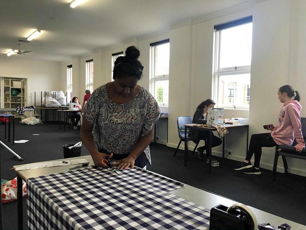 Стол раскроя и швейные машины на заднем плане, где группа женщин работала над пошивом формы для животных, обожженных во время лесных пожаров. [Фото: Джош Вуд]