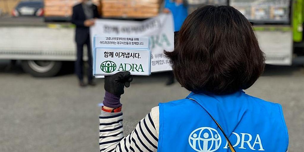 """Сотрудник ADRA держит наклейку с надписью """"Давайте преодолеем вместе"""". [Фото: ADRA Южная Корея]"""