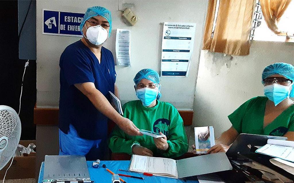 Абель Залданья (слева) передает миссионерскую книгу «Надежда среди хаоса» медицинскому персоналу Орбелисии де Моралес и Сабрине Гонсалес в национальной больнице в Ла-Унион, Сальвадор. Адвентисты седьмого дня в восточной части этой центральноамериканской страны, начиная с 18 июля 2020 г., раздали оздоравливающие напитки и книги тысячам передовых работников в четырех больницах Сан-Мигеля. [Фото: Конференция Восточного Сальвадора]
