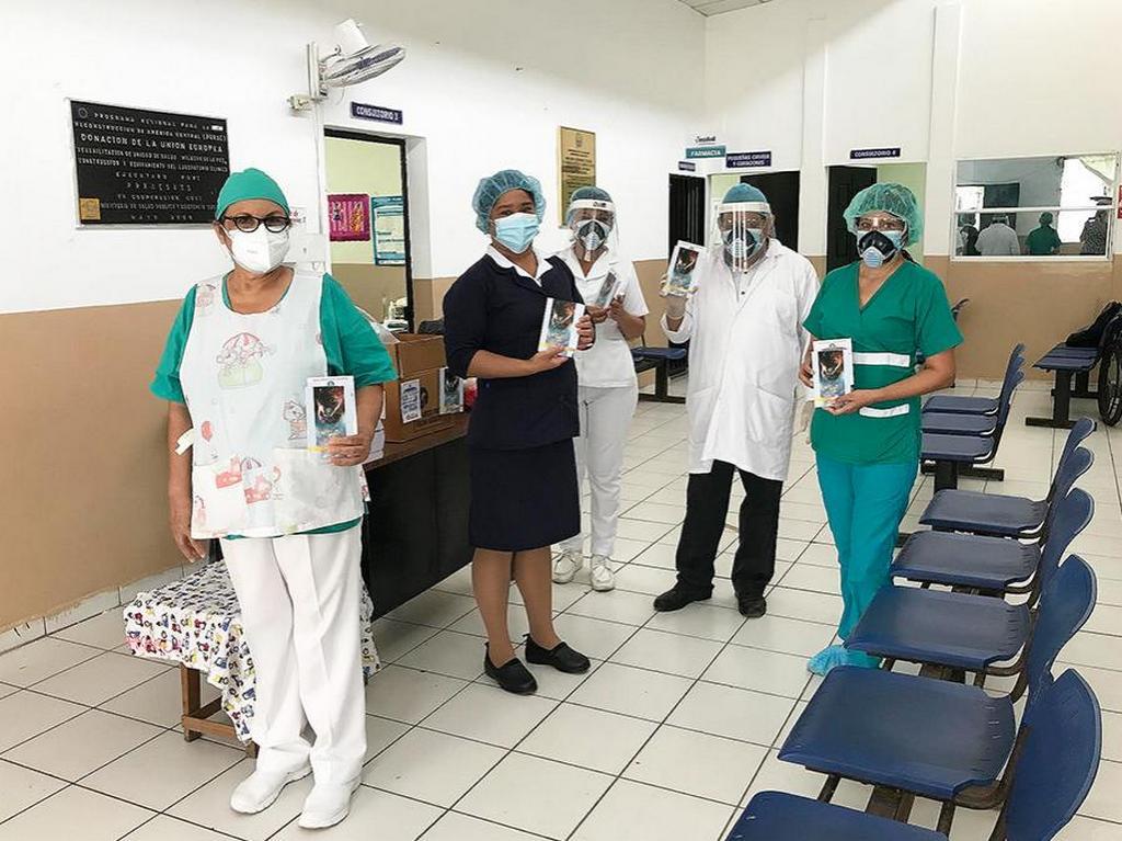 Медсестра-адвентистка Рейна Ривас (справа) держит миссионерскую книгу, которую она передает врачу Хосе Роберто Крус (второй справа) вместе с медсестрами и персоналом больницы в больнице социального обеспечения в Сан-Мигеле, Сальвадор. [Фото: Конференция Восточного Сальвадора]