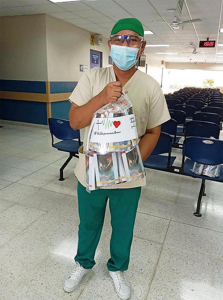Медицинский работник Уильям Франко держит подаренные пакеты с книгами и напитками в больнице социального обеспечения в Сан-Мигеле, Сальвадор. [Фото: Конференция Восточного Сальвадора]