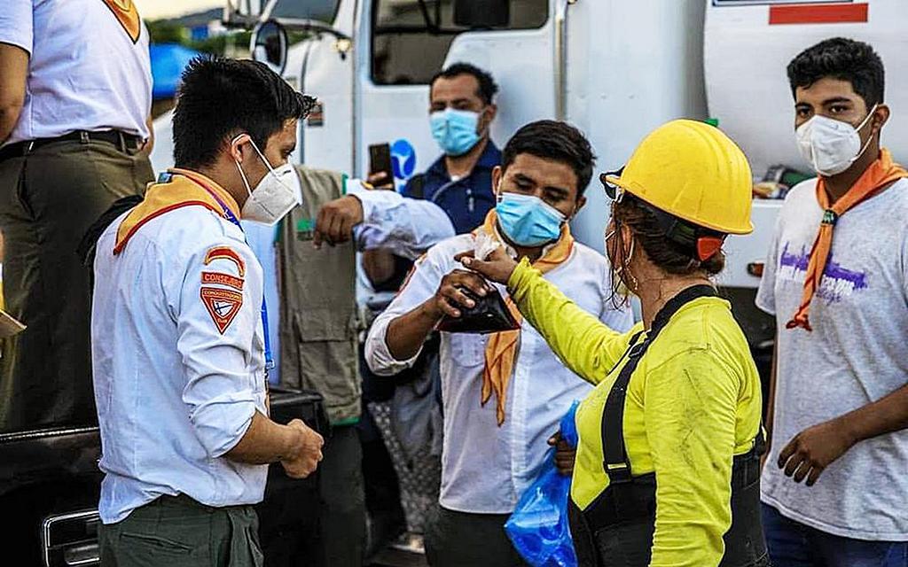 Мастер-проводники и следопыты с северо-запада Сальвадора раздают угощение работнику по уборке мусора в Неджапе. [Фотография любезно предоставлена Унионом Сальвадора]