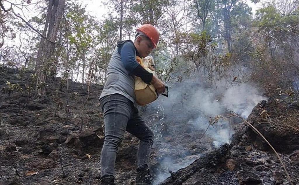 Мастер-проводник помогает тушить очаги лесных пожаров, спаливших сотни акров в горном районе Морасана, Сальвадор, в марте 2021 года. Группа мастеров-гидов вызвалась на несколько дней, чтобы помочь пожарным, государственным служащим и другим добровольцам, чтобы помочь спасти деревни, которым угрожает пожар. [Фото: Унион Сальвадора]