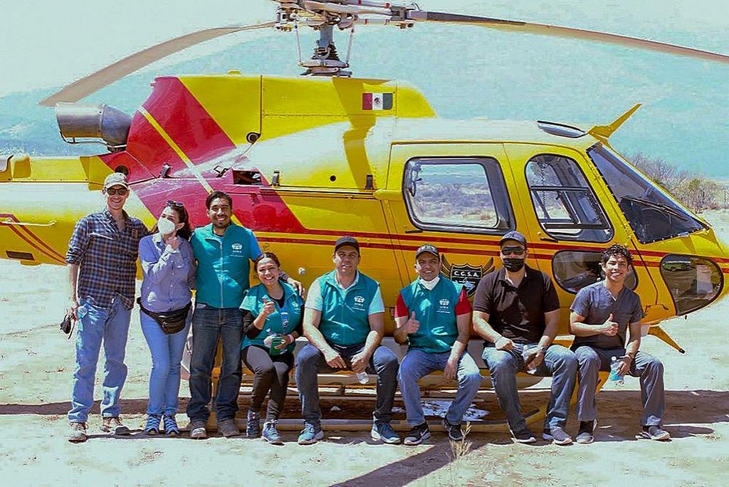 Группа аварийно-спасательных служб и добровольцы ADRA North Mexico позируют перед вертолетом, который помогал контролировать пожар в Восточном регионе Сьерра-Мадре. [Фото: любезно предоставлено Маноло Асеведо]