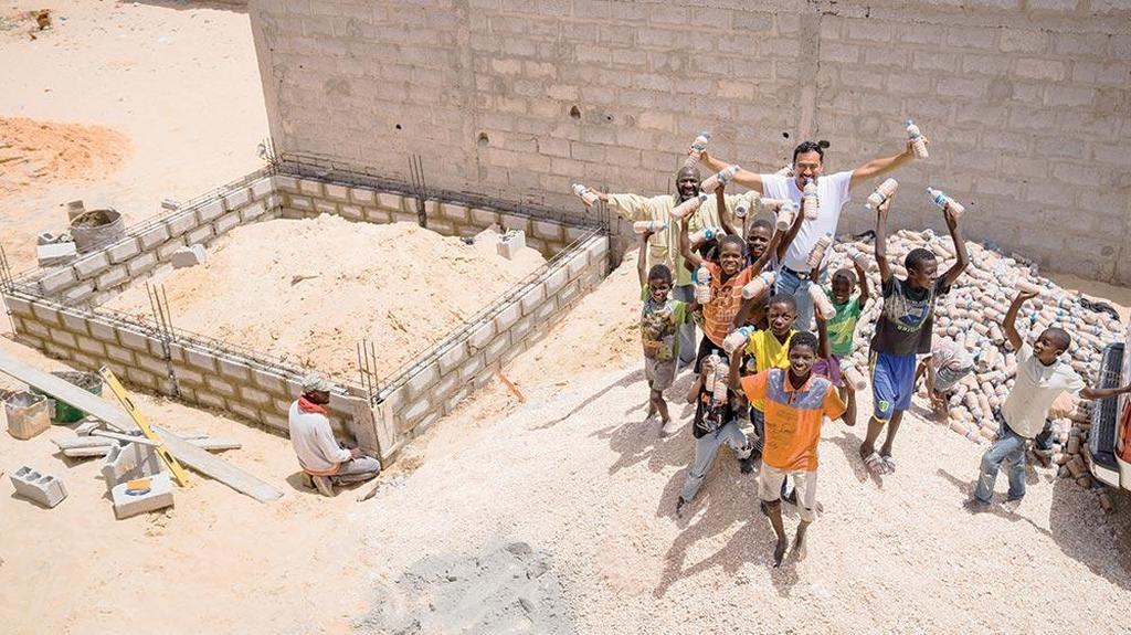 Прогресс достигнут в строительстве фундамента дома, а соседские дети и директор ADRA в Мавритании Андре Саенс, одетый в белую футболку, демонстрируют бутылки с водой, используемые для строительства. [Фото: Адвентистская миссия]