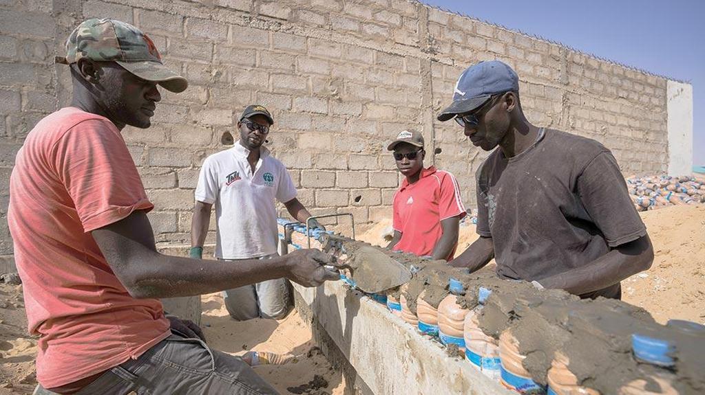 Каменщики изучают технику строительства из бутылок с водой. [Фото: Адвентистская миссия]