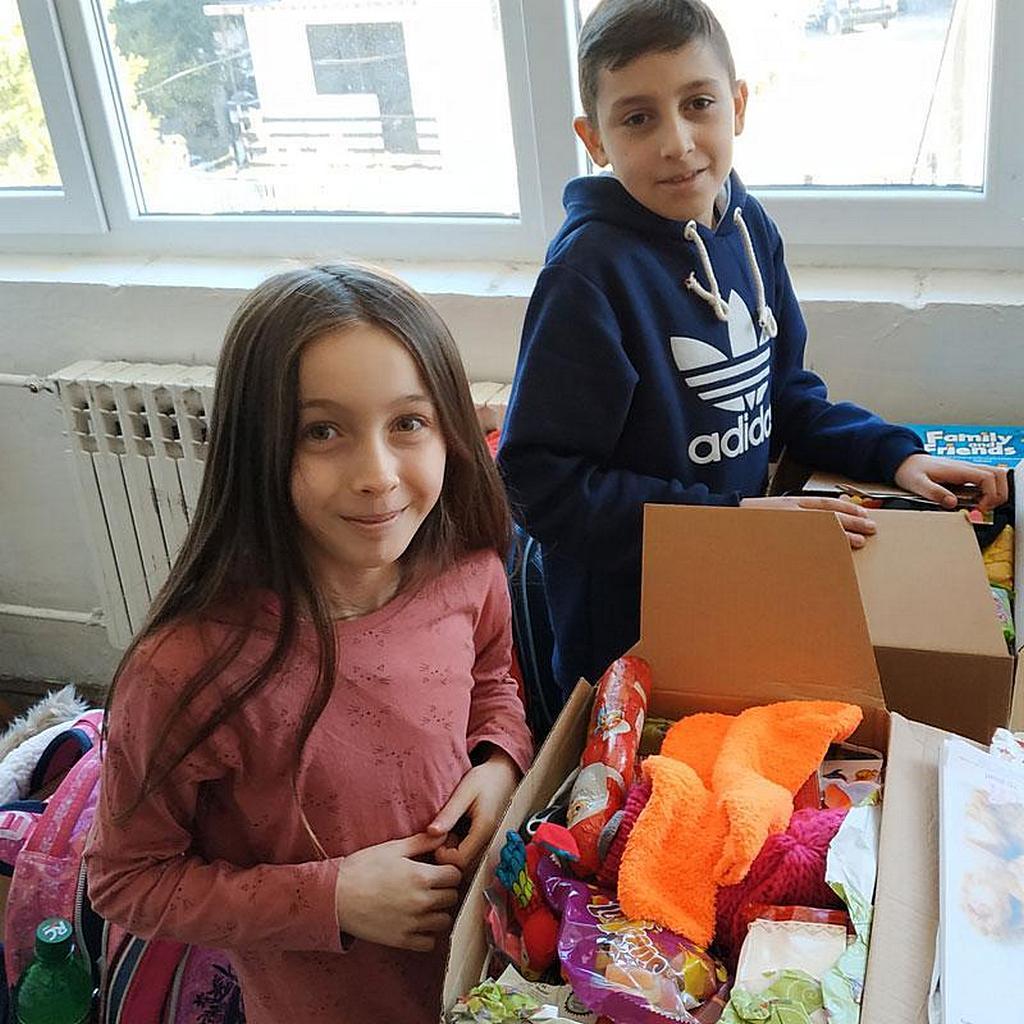 """Дети открывают посылки, отправленные Адвентистским агентством развития и помощи в Германии в рамках инициативы """"Дети помогают детям"""". [©Фото: ADRA Deutschland eV]."""