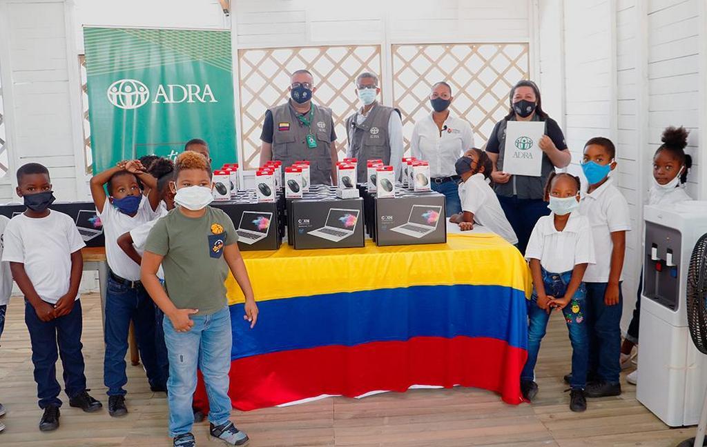 Руководители Адвентистского Агентства Развития и Помощи стоят с детьми, когда они делают групповое фото на фоне новых компьютеров, которые будут использоваться в школе Бомбона на острове Провиденсия, 13 июля 2021 года. (Фото: ADRA Colombia)