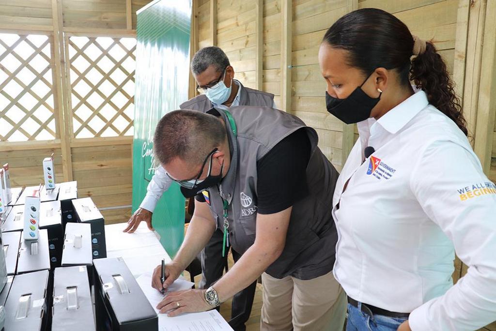 Хаир Флорес (слева), директор ADRA Колумбия, подписывает документ о передаче 90 компьютеров пяти школам на колумбийских островах. Лусила Моралес (справа) из офиса Министерства образования и Эдгар Редондо (сзади), президент Конференции униона Северной Колумбии Адвентистской церкви, смотрят на происходящее в образовательном учреждении Хунин 13 июля 2021 г. [Фото: ADRA Colombia].