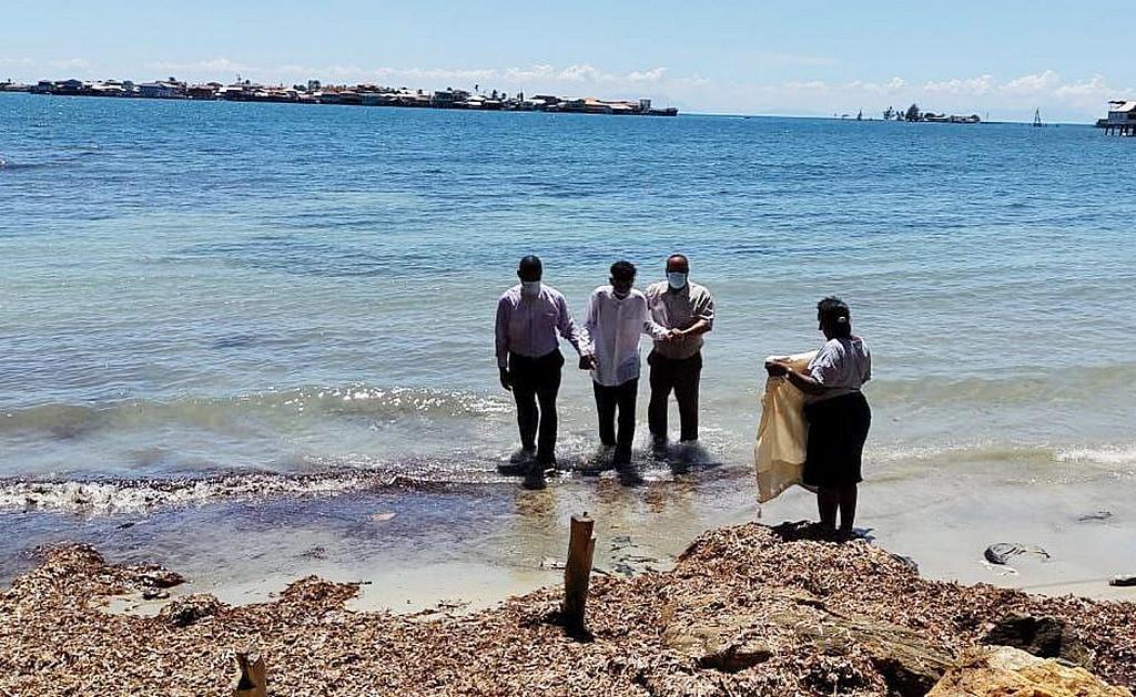 Симеону Габриэлю МакЛину (в центре) помогают выбраться из воды после крещения в субботу 2 октября, на крошечном островке, расположенном напротив места пожара в Гуанахе. В ближайшие недели планируют принять крещение еще несколько человек. (Фото: Даниэль Татум)