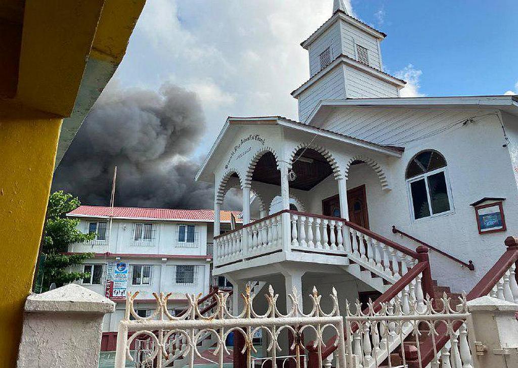 Вид на адвентистскую церковь и школу в Гуанахе до того, как пожар охватил третий этаж школы 2 октября 2021 года. Деревянная церковь осталась невредимой. [Фото: Конференция островов Бэй].