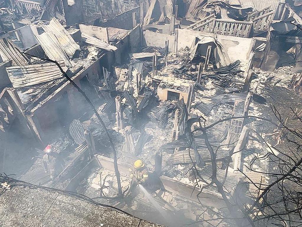 Пожарный поливает стены домов и предприятий, сгоревших ранее днем 2 октября 2021 года, рядом со школой адвентистской церкви. (Фото: Джони Джим Сантос)